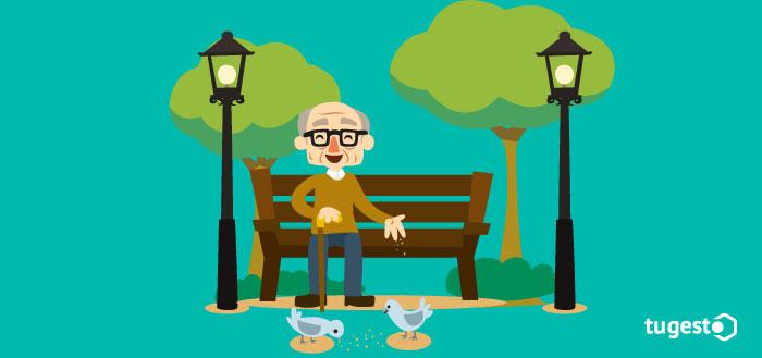 jubilado sentado en un banco dando de comer a las palomas